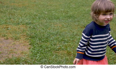 Happy smiling young toddler little girl walking outside in...