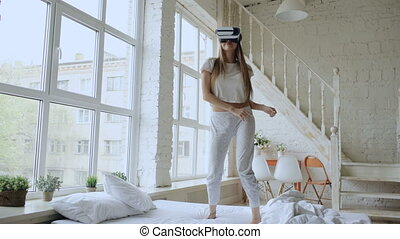 Happy smiling young woman dancing while getting experience using 360 VR headset glasses of virtual reality on bed at home