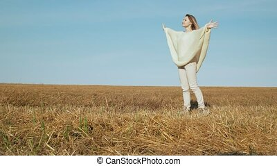 Happy smiling young woman enjoying nature on harvesting field.