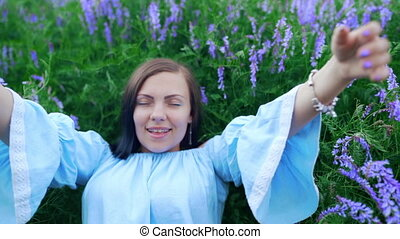 Happy smiling young woman falling down on grass with violet...