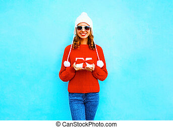 happy smiling young woman holds gift box in hands on a blue background