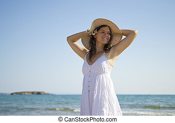 Happy smiling young woman next to the sea