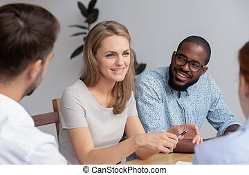 Happy smiling young woman talking with coworkers at work