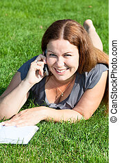Happy smiling young woman with book speaking by phone on green grass