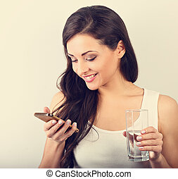 Happy smiling young woman with healthy skin reading and writing in mobile phone sms and drinking clean water. Consulting the diet. Closeup toned portrait.