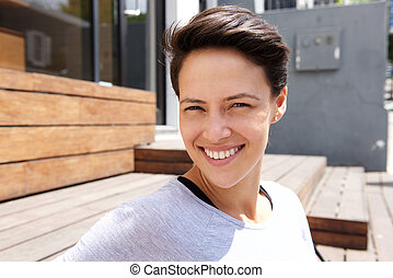 Happy smiling young woman with short hair