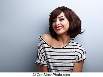 Happy smiling young woman with short hair on blue copy space...