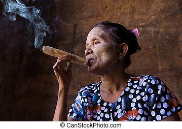 happy smoking old woman in myanmar