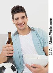 Happy soccer fan watching tv