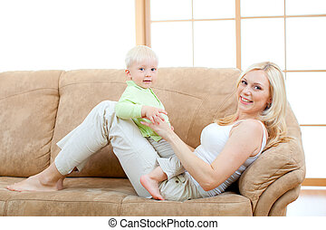 Happy son and mother lying on sofa looking directly to...
