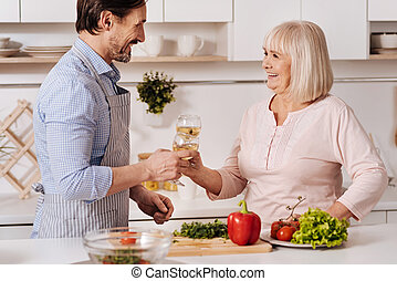 Happy son enjoying wine with his parent in the kitchen