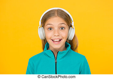 Happy song makes her smile. Happy small girl listen to music on yellow background. Little child enjoy song playing in headphones. Smile on happy face. Music has happy emotions