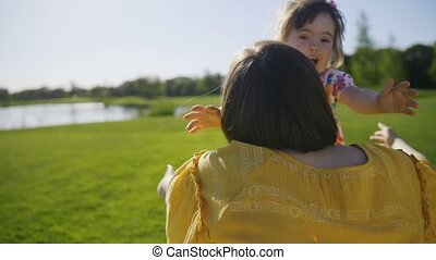 Happy special needs girl running and embracing mom - Happy...