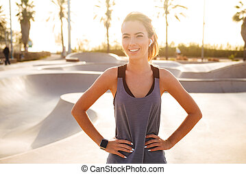 Happy sports lady standing outdoors listening music