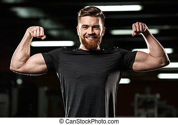 Happy sports man showing his biceps.