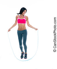 Happy sports woman jumping with skipping rope - Full length...