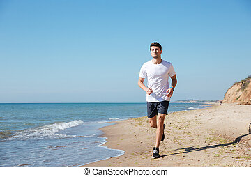 Happy sportsman running on the beach - Happy handsome young...