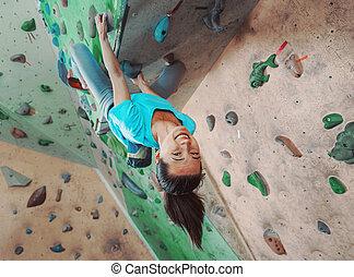 Happy sportswoman climbing indoor - Happy young woman ...