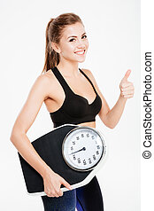 Happy sportswoman holding weight scales and showing thumbs ...