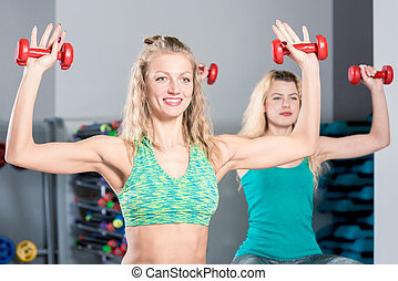 happy sportswoman with dumbbells during training in the gym