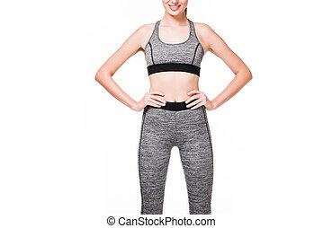happy sportswoman with hands on waist