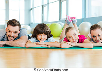 Happy sporty family. Happy family bonding to each other while lying on exercise mat in sports club