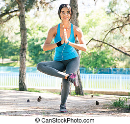 Happy sporty woman doing yoga exercises