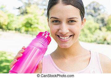 Happy sporty woman holding water bottle