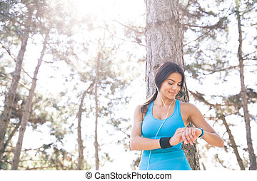 Happy sporty woman using smart watch outdoors in park