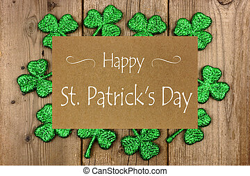 Happy St Patrick Day greeting card with shiny shamrocks over rustic wood