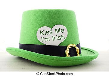 Happy St Patricks Day green leprechaun hat on white wood table with Kiss Me I am Irish heart shape greeting sign.