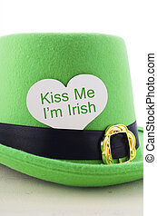 Happy St Patricks Day green leprechaun hat on white wood table with Kiss Me I am Irish heart shape greeting sign, vertical.