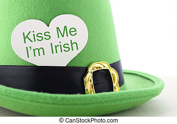 Happy St Patricks Day green leprechaun hat on white wood table with Kiss Me I am Irish heart shape greeting sign, closeup.