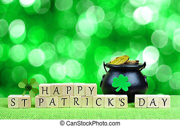Happy St Patricks Day wooden blocks with Pot of Gold and shamrock over twinkling green background