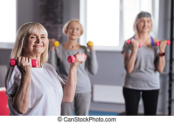 Happy strong woman standing with dumbbells