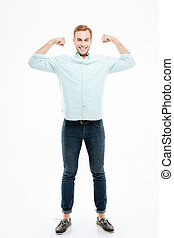 Happy strong young man standing and showing biceps