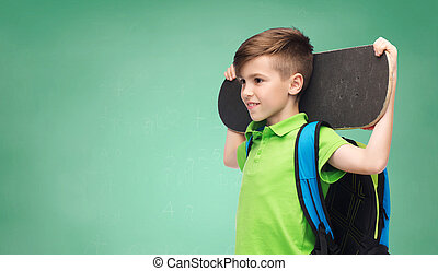 childhood, school, education and people concept - happy smiling student boy with backpack and skateboard over green school chalk board background