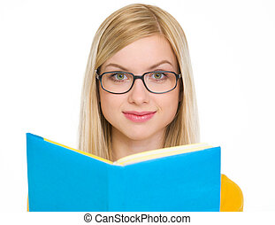 Happy student girl reading book in glasses
