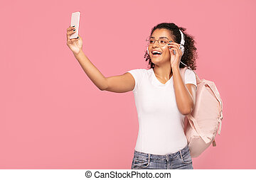 Happy student girl with backpack and mobile phone.