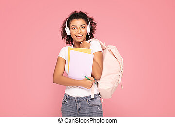 Happy student girl with backpack and notebooks.