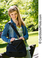 Happy student girl with bag standing outside