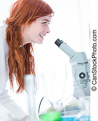 happy student in chemistry lab - side-view of a student in a...