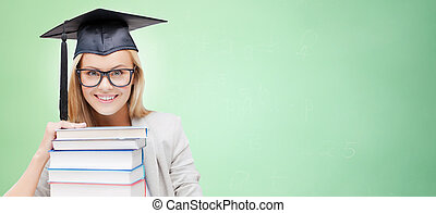happy student in mortar board cap with books - education, ...