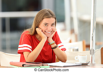 Happy student posing in a coffee shop