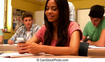 Happy student sending a text in class