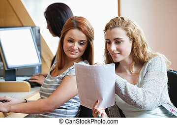 Happy student showing her notes to her classmate