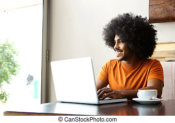 Happy student sitting at table with laptop