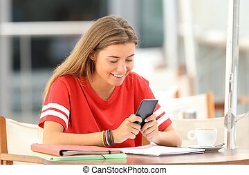 Happy student using a smart phone in a restaurant