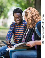 Happy Student Using Digital Tablet With Friends On Campus