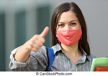 Happy student wearing mask with thumbs up